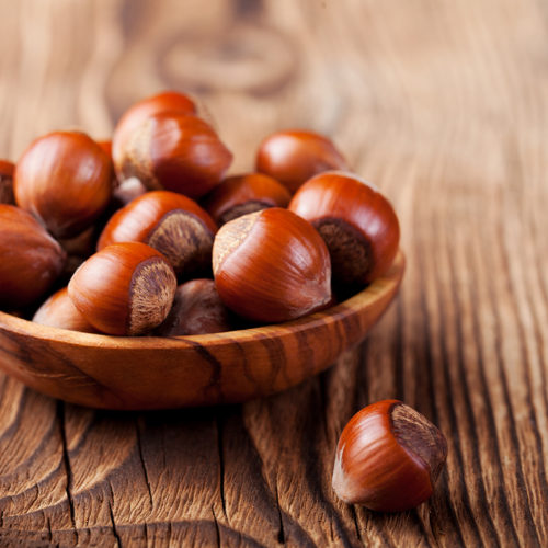 Hazelnuts in a wooden bowl on a wooden background. copy space